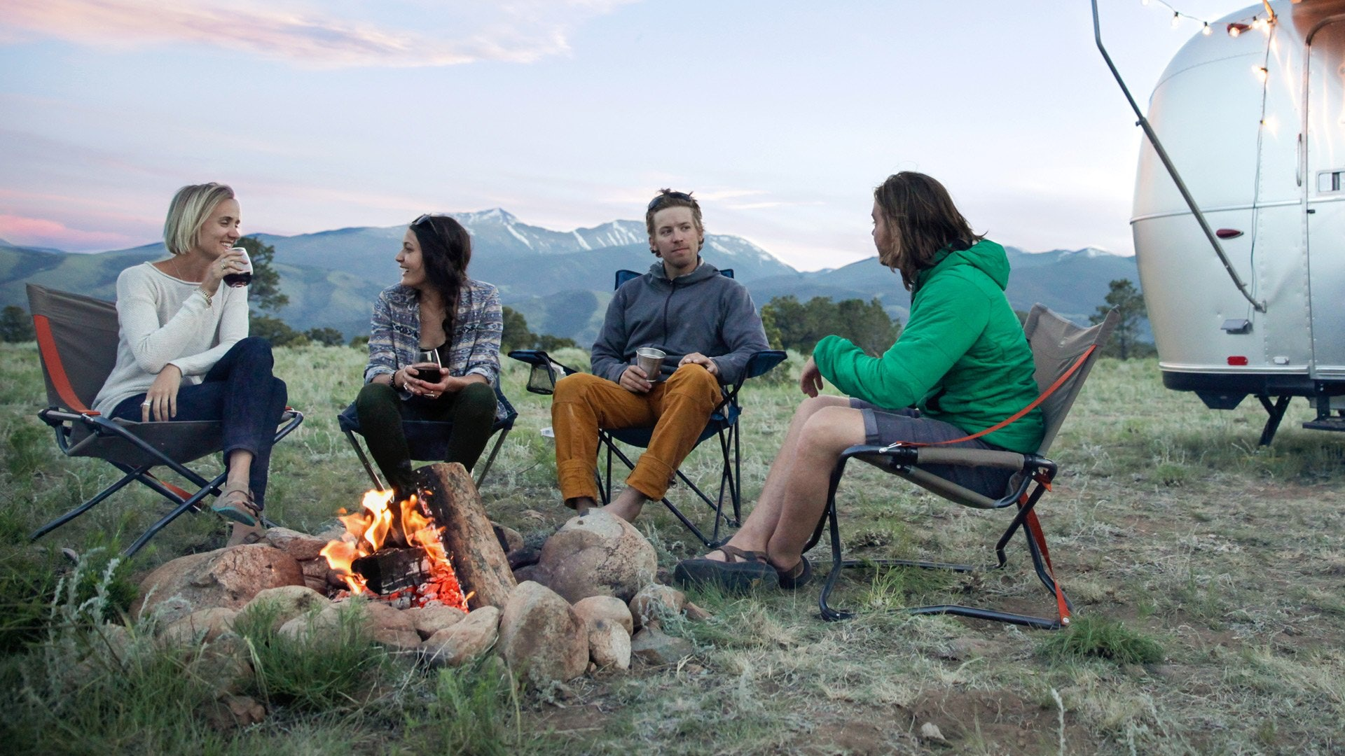 four millennials around a campfire with airstream in the background