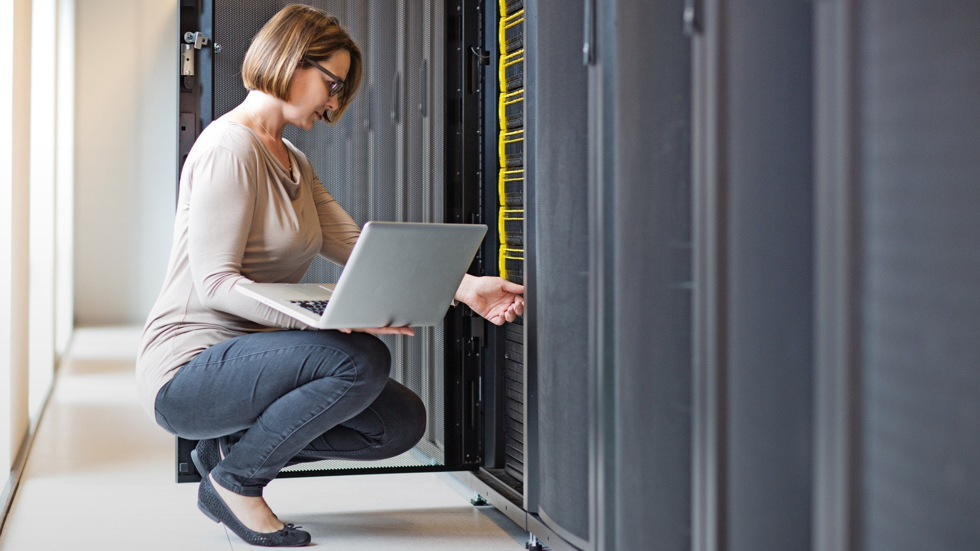 blonde woman with computer crouching down