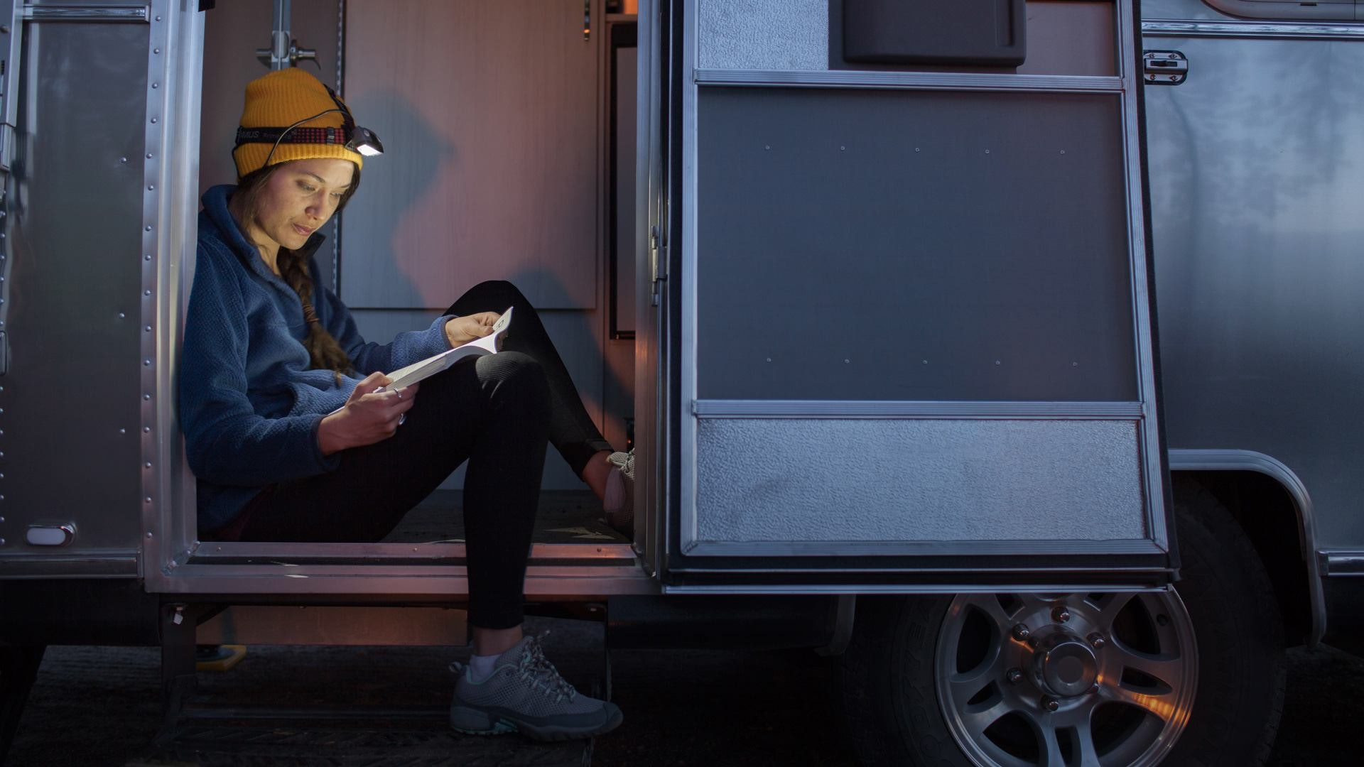 girl sitting in door of airstream with flashlight