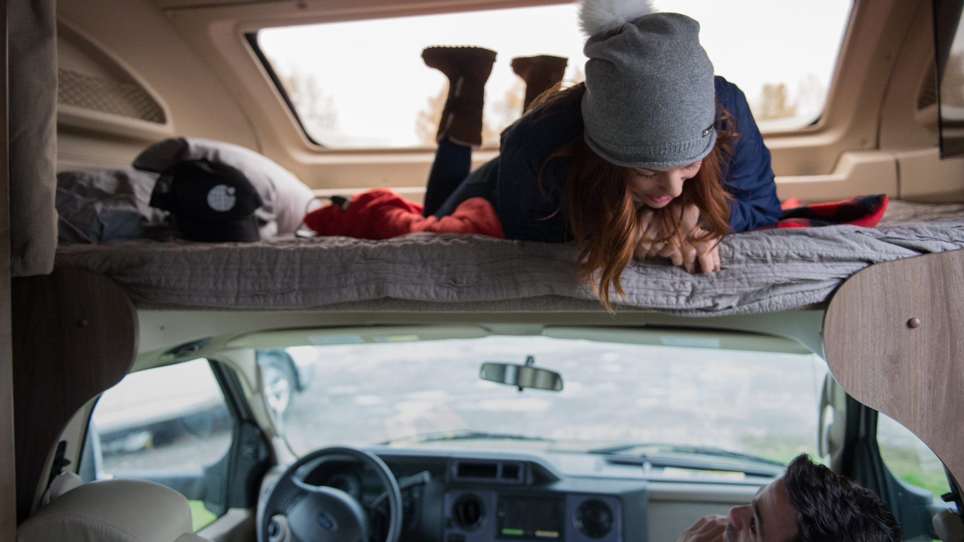 woman in roof top tent talking to man in car