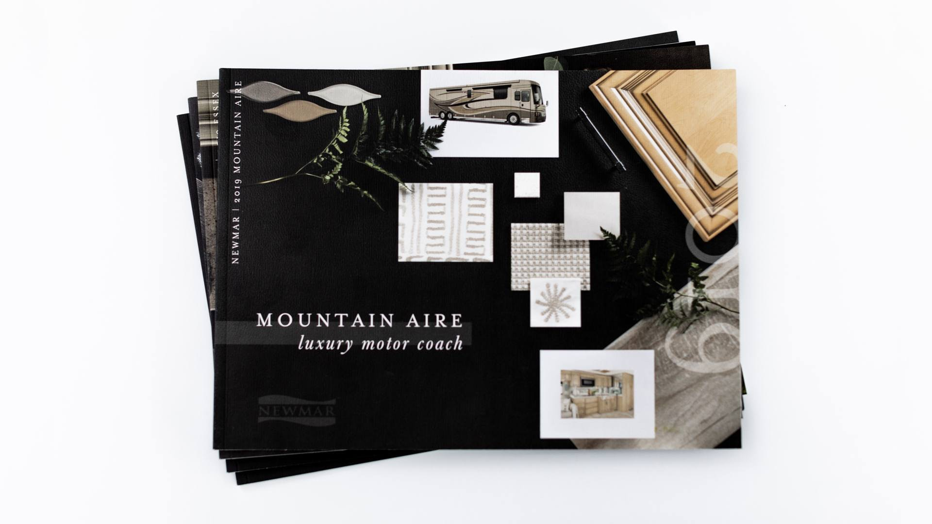 stack of product brochures for mountain aire newmar rv